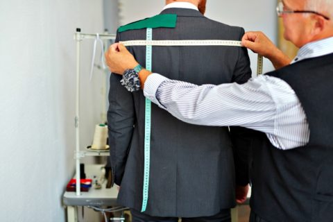 Getting fitted for a suit jacket - suit fitting with a tailor
